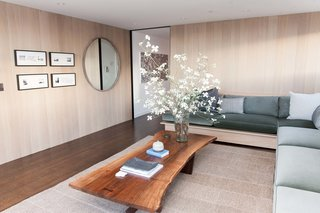 "The penthouse living room and bar by Catherine Kwong features a Nakashima Cocktail Table. Kwong flew to Pennsylvania to meet with George Nakashima's daughter, Mira, and selected the slab of walnut that would anchor the room. ""That was the first design decision made, and everything else followed,"" says the designer."