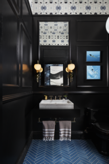 "Designed by Benni Amadi Interiors and Courtney Springer Interiors, the ""Moody Blues"" powder room and vestibule pairs a marble sink with dramatic black walls that make the room seem more spacious, while blue tiles laid in a herringbone pattern reference the traditional architecture of  the home."