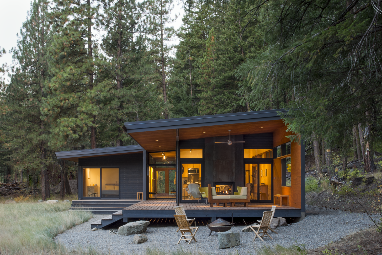 Exterior, Cabin Building Type, Wood Siding Material, and Glass Siding Material In Washington's Methow Valley, a modern cabin with an outdoor living room allows views of the surrounding woodland and meadow to perforate its volume.   By day, the Chechaquo Lot 6 cabin gives the impression of floating in a forest clearing; by night, its windows glow against the wooded darkness. From all vantage points, the landscape permeates this 1,000-square-foot cabin, designed for two outdoor enthusiasts and tucked at the toe of a dramatic slope in Winthrop, Washington.  Photo 2 of 10 in A Lean Cabin in Washington Dismantles the Indoor/Outdoor Divide