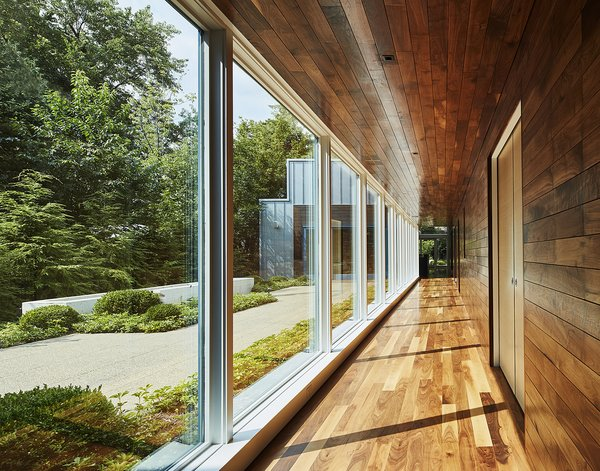 A stunning wall of windows creates a cloister-like feel adjacent to the main courtyard. The outdoor spaces