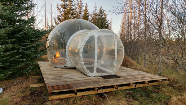 Smaller bubbles come with a round bed that sleeps two, while the larger units have a double bed. Guests share a wood-clad outbuilding that holds the restroom, showers, and kitchen. Adventurers can also book the Golden Circle Tour through Buubble, exploring Thingvellir National Park, the Geysir hot springs, Gullfoss waterfall, and the Secret Lagoon before spending a night at the hotel.