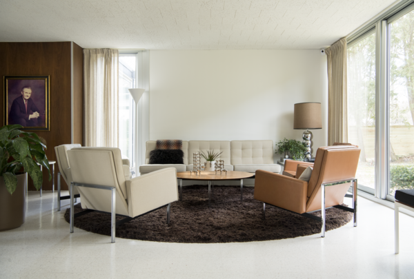 A Knoll Parallel Bar Sofa, Lounge Chairs, and Coffee Table outfit the living room along with a Nessen Studios Torchiere Floor Lamp.