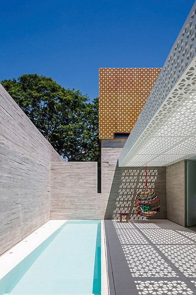 Located in São Paulo, Brazil, this serene outdoor space is part of the Aigai Spa, which was designed by figueroa.arq, but it could just as easily be someone's home. The elongated pool runs the length of the patio and at one end hangs a multicolored swinging chair.  Photo courtesy of Leonardo Finotti