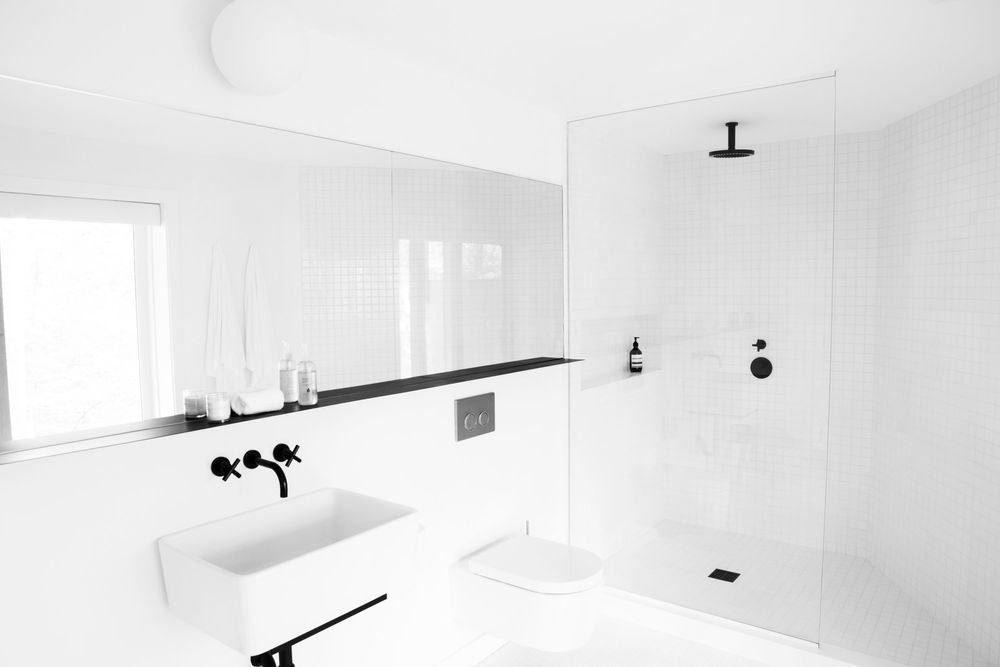 This Hamptons home was designed by Amee Allsop with fresh, all-white tiles and contrasting black fixtures which result in a crisp and clean feel.  Photo by Glen Allsop  Bathroom from 10 Minimalist Bathrooms of Our Dreams