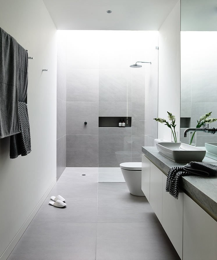 Melbourne is the location of the Canny-designed Lubelso Hawthorn Concept Home where one of the bathrooms has large, soft grey tiles on the floor that continue up the sides of the shower walls. A skylight above the shower keeps the space full of light.  Photo by Derek Swalwell  renovation from 10 Minimalist Bathrooms of Our Dreams