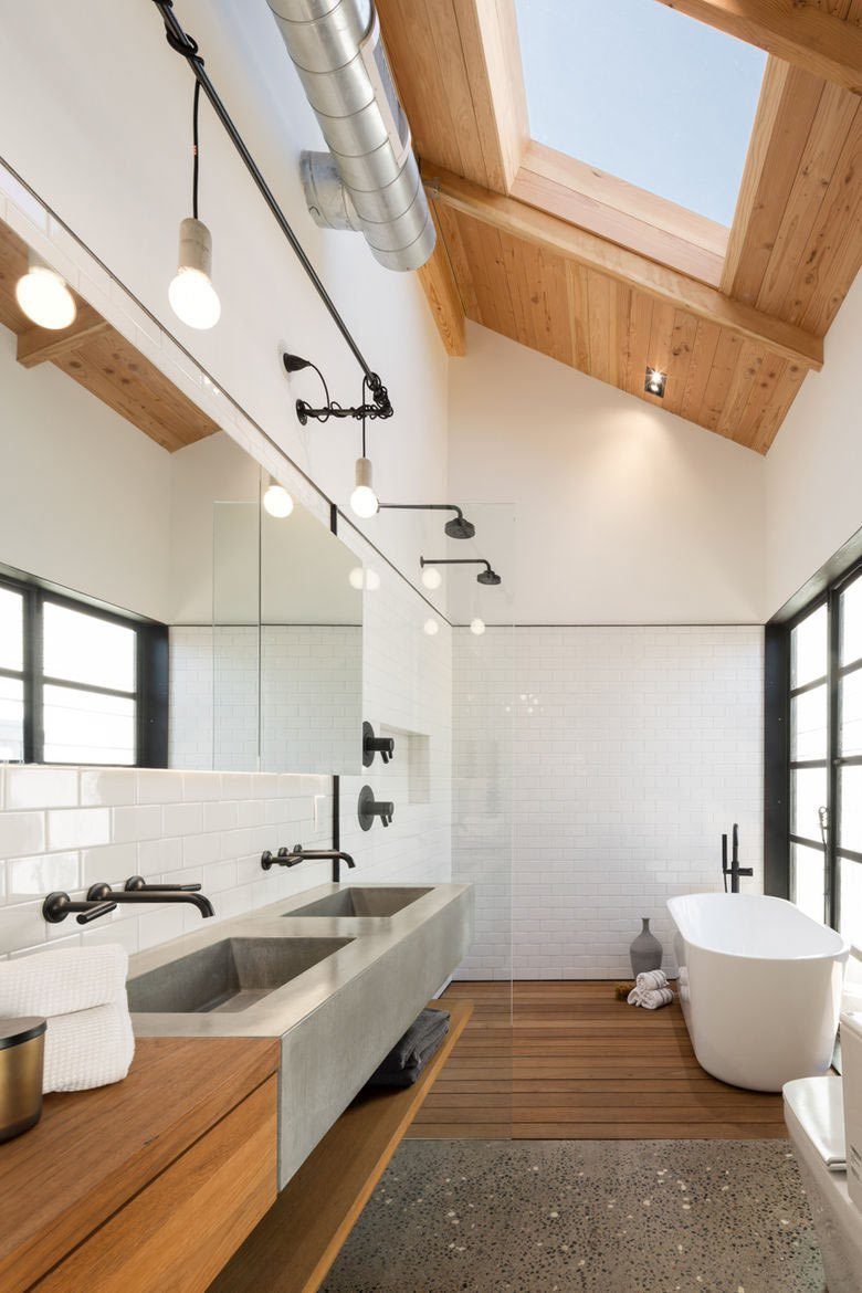 Designer Joel Contreras hired architect neighbor Jonah Busick, of Foundry12, to renovate his 1927 bungalow in Phoenix. The large bathroom got a modern overhaul with a skylight that illuminates the space, along with a new white tub from Brizo, black fixtures, wooden elements, and a concrete double basin from SlabHaus.  Photo by Jason Roehner  Bathroom dreams from 10 Minimalist Bathrooms of Our Dreams