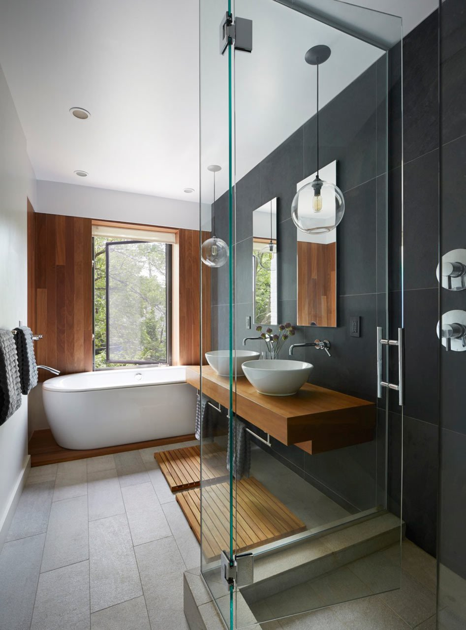 In Brooklyn's Prospect Heights, this townhouse by Etelamaki Architecture has a spa-like bathroom with mixed materials that include a slate wall behind the double sinks, which are suspended on a teak vanity. The freestanding tub sits on a raised wooden bed that continues up the wall behind it.  Photo by Mikiko Kikuyama  Bathroom insperation from 10 Minimalist Bathrooms of Our Dreams