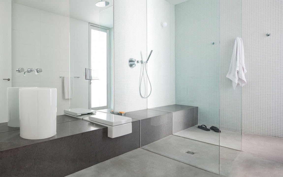 The Russet Residence, located in West Vancouver, British Columbia, has a minimalist bathroom that comes with some really cool features. Designed by Splyce Design, the space features polished concrete floors, a shower separated by only two walls of glass, a cylinder sink basin, and a toilet built into the elongated bench.  Photo by Ivan Hunter  Bathroom from 10 Minimalist Bathrooms of Our Dreams