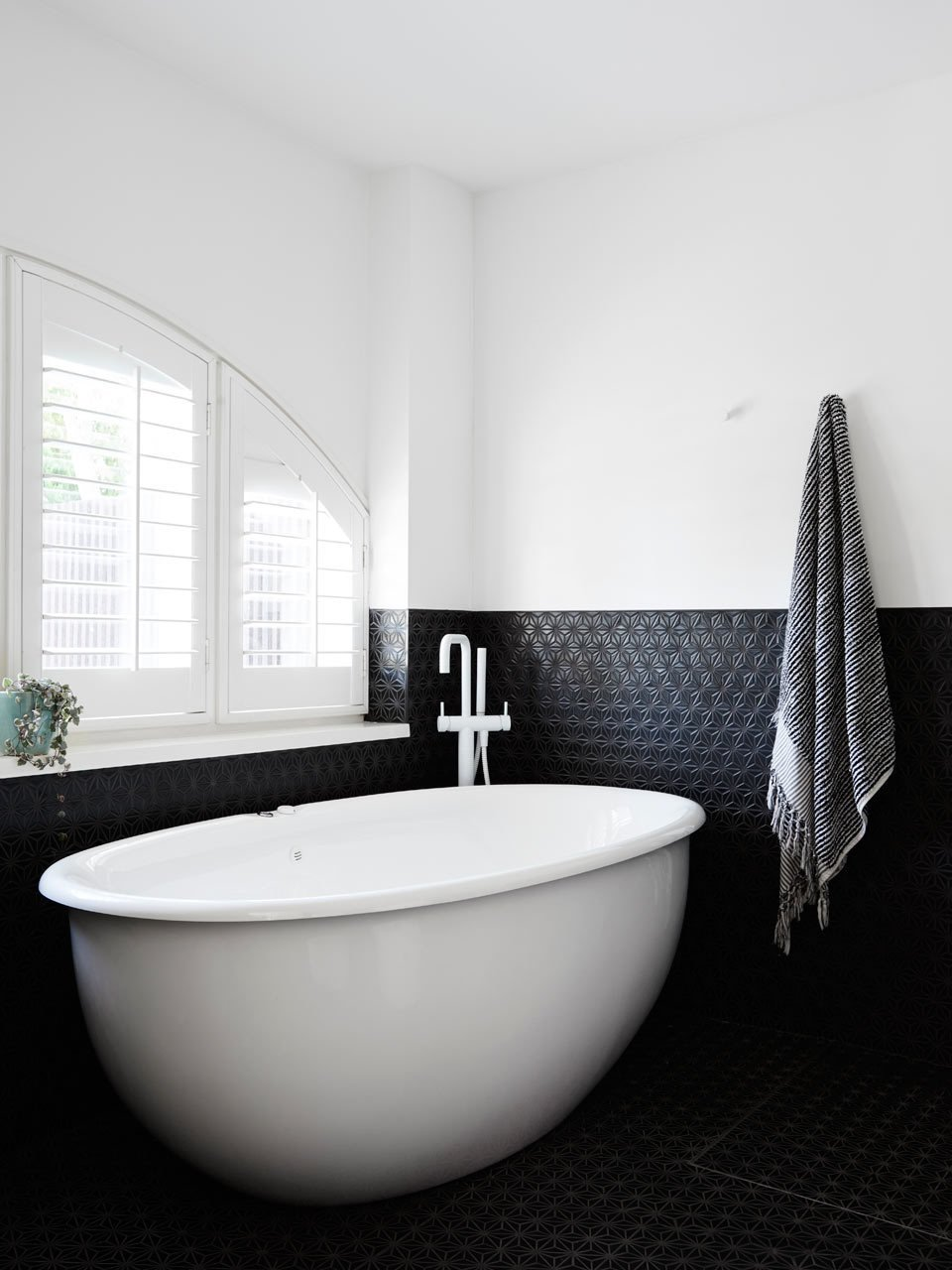 #designmilk #northbourne #architecture #melbourne #modern Photo by Eve Wilson  The new master bathroom is outfitted with charcoal Japanese mosaic tiles, which contrast the white paint and fixtures.    Tubs
