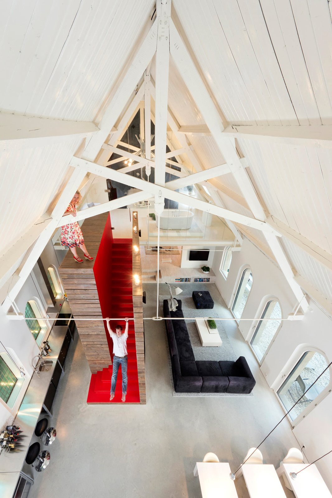 Located in Harrlo, The Netherlands, this home was once the Dutch Reformed Evangelism Building before being transformed by Leijh Kappelhoff Seckel van den Dobbelsteen architecten. The new design includes a bedroom and bathroom loft with modern features and furnishings paired with many of the original details, including the wood roof and the arched stained glass windows.  Photo 2 of 10 in Traditional Churches Become Modern Homes