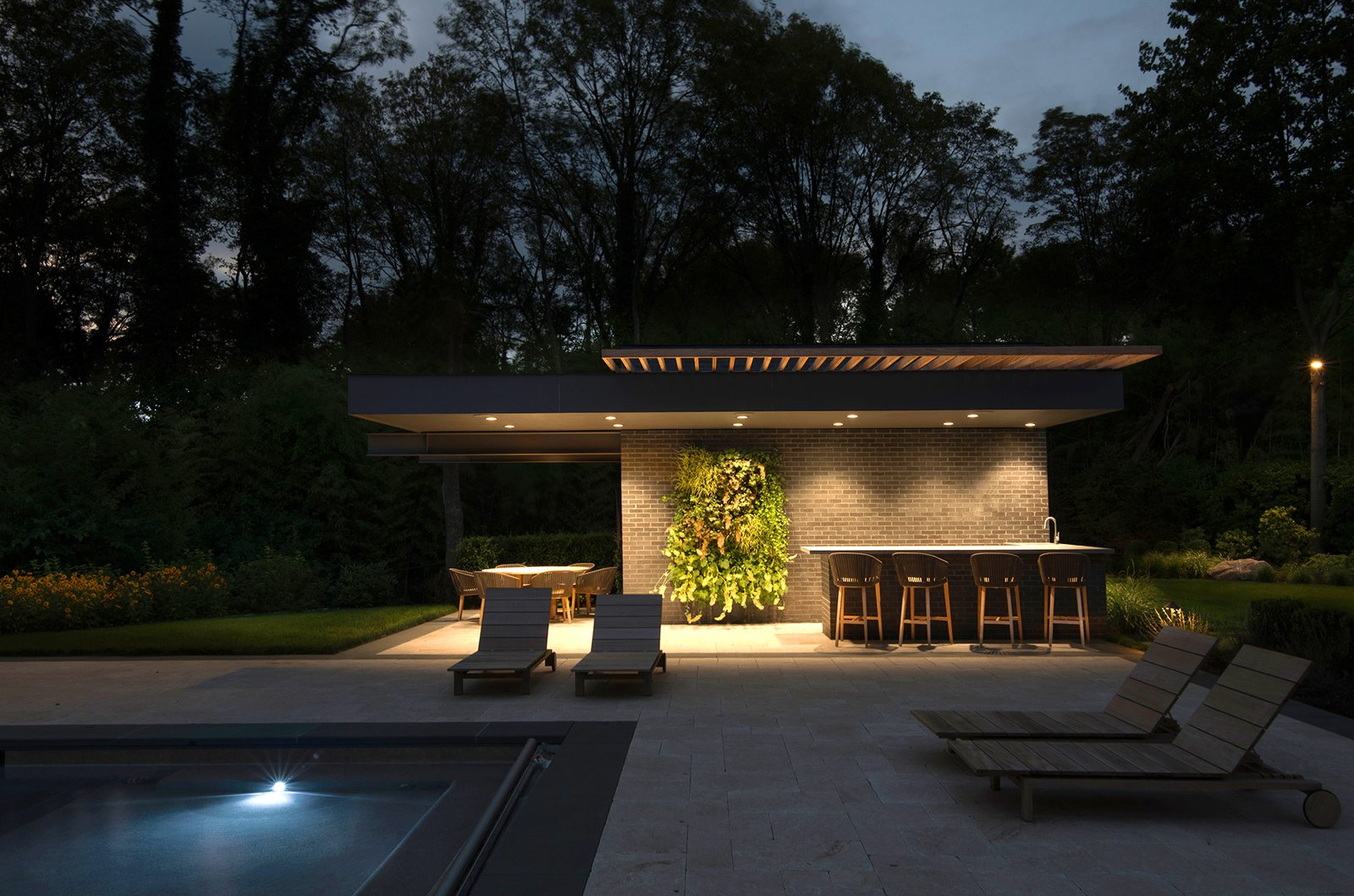 Lighting at UP Studio's Free Float Pool House creates a dramatic setting for entertaining at night.  Free Float Pool Cabana by The UP Studio