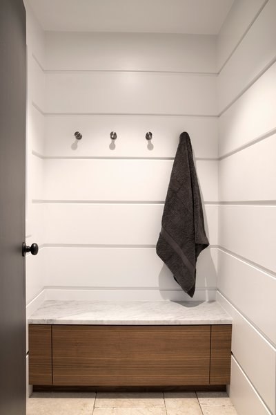 The Free Float Pool House's interior changing room features white wall panels with reveals for visual interest.  Free Float Pool Cabana by The UP Studio