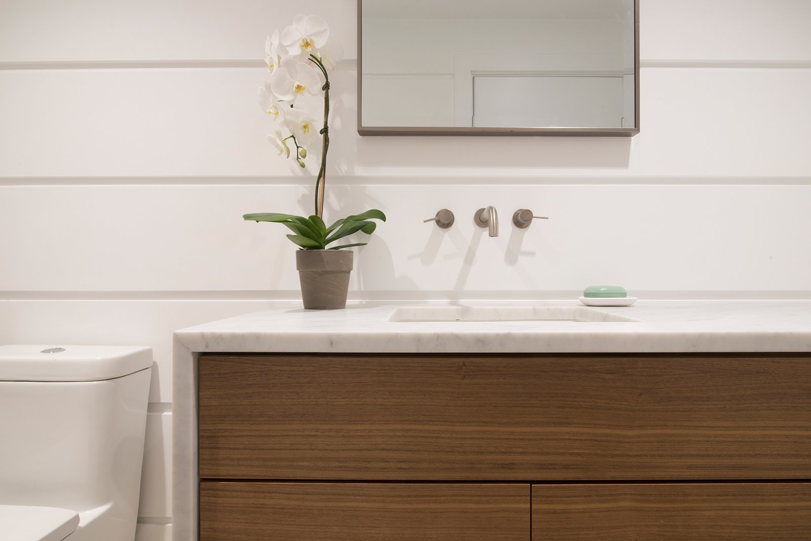The cabana bathroom's custom vanity provides storage with a contemporary feel.  Free Float Pool Cabana by The UP Studio