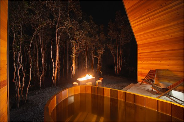 Cedar soaking tub and fire pit at night