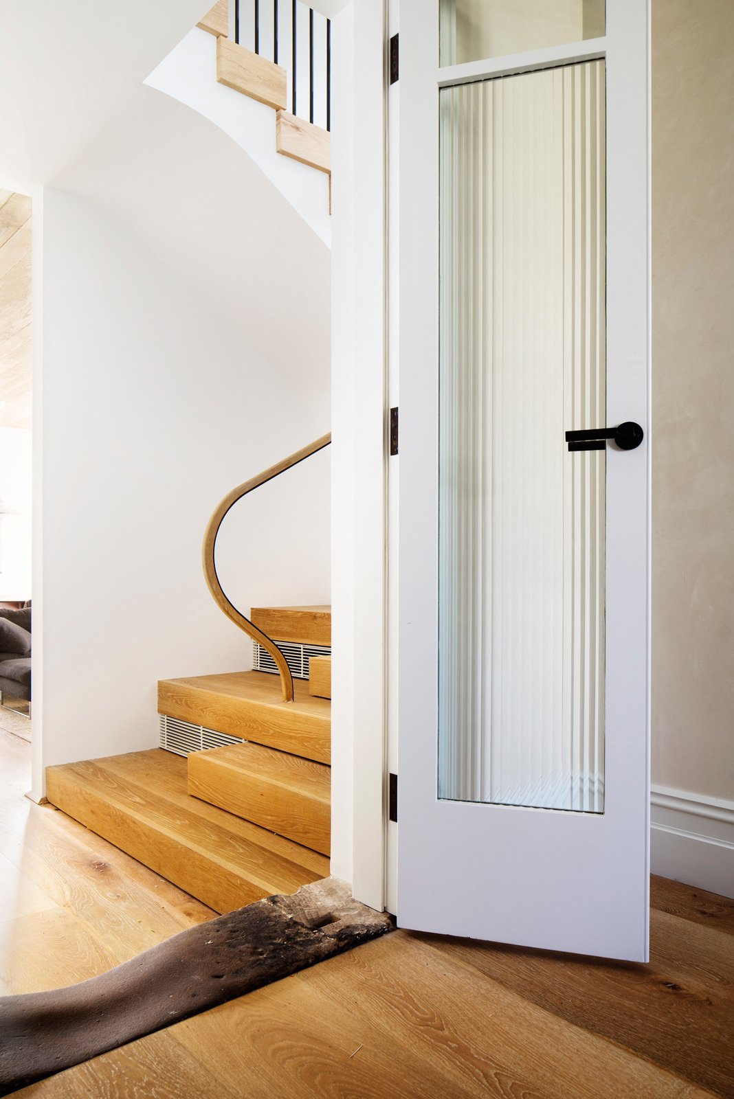 The original stone door sill that linked the front of the house to the back kitchen and Victorian outhouses. It links the new to the old, a new stair is visible in the background. © Justin Alexander  Loggia in Arcadia by Luigi Rosselli Architects