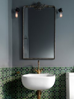 Brightly-colored encaustic tile has a matte finish that contrasts with the glossy white of the bathroom fixtures.