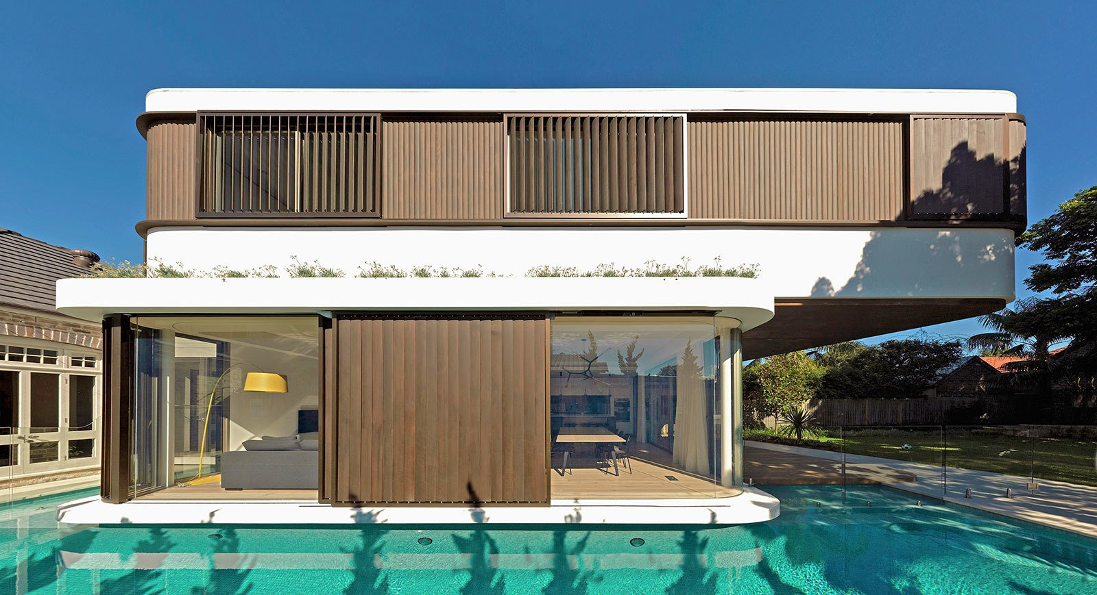 The first floor bedrooms cantilever towards the backyard, being larger than the ground floor living spaces. The two rectangular volumes are shifted, each with different wall constructions: very glazed and open downstairs, and closed upstairs. The bedrooms have two sliding shutters, manually controlled. © Justin Alexander  The Pool House by Luigi Rosselli Architects