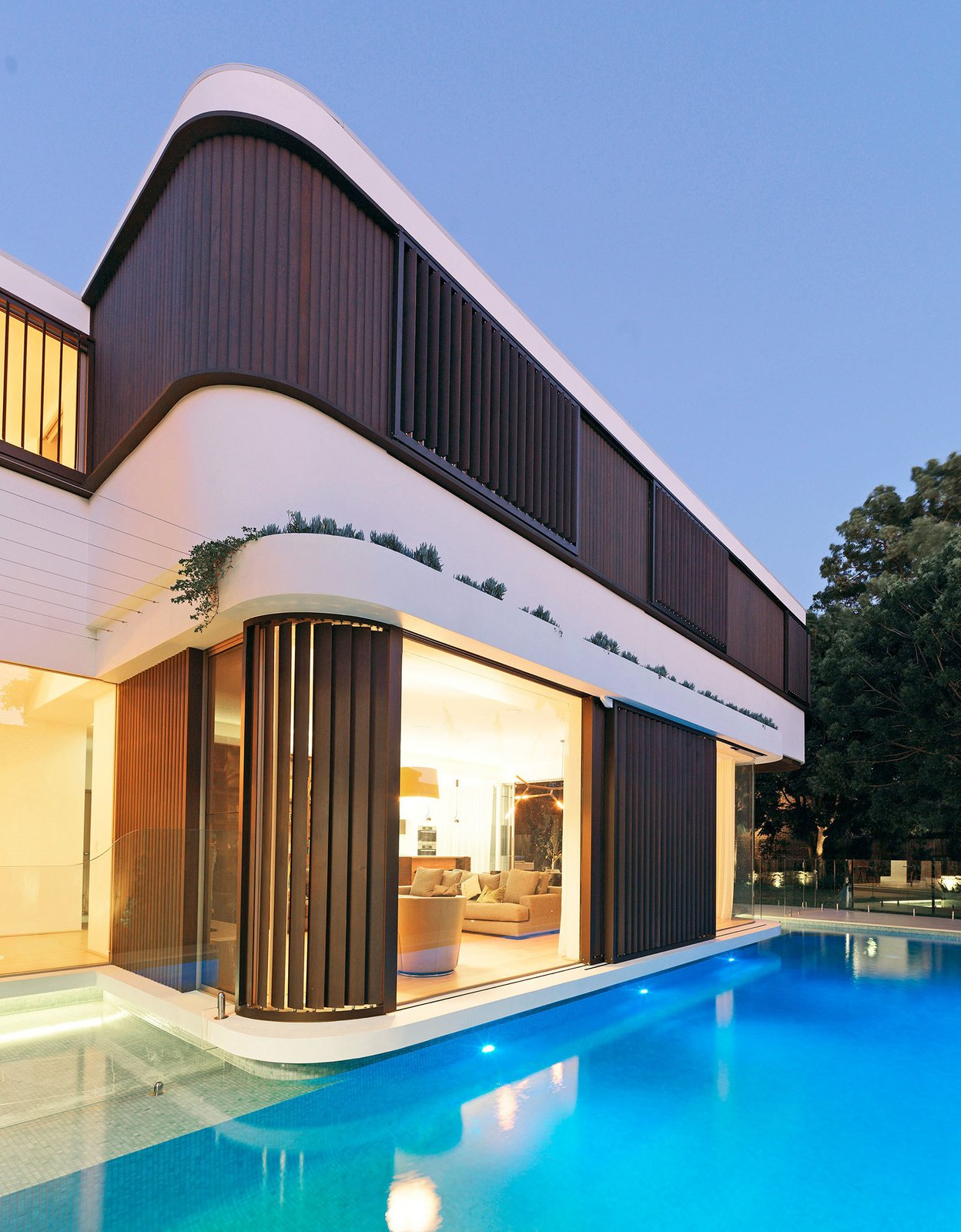 """By dividing the first floor walls in three strips, the horizontality is reinforced; a lower structural spandrel below the windows, finished with an acrylic white render, a middle window strip with timber shutters and timber """"log cabin"""" weatherboards, and an upper roof edge also finished with an acrylic render. © Justin Alexander  The Pool House by Luigi Rosselli Architects"""