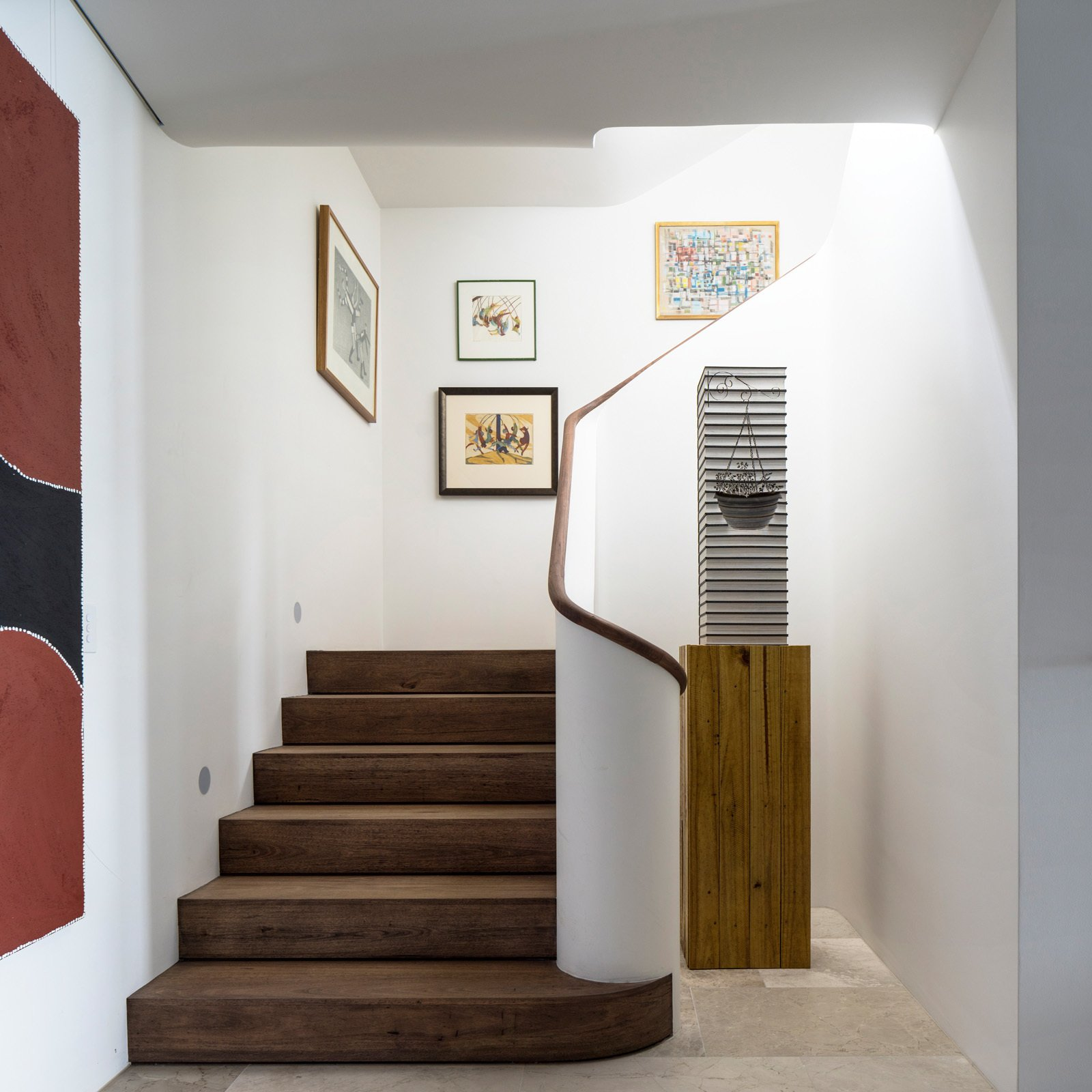 The vertical gallery of paintings terminates at the bottom of the stairs with a sculpture. © Justin Alexander  Harbour Front-Row Seat by Luigi Rosselli Architects