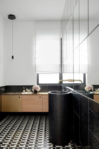 Another bathroom boasts a striking black-and-white patterned tile on the floor and is completed with gold faucets, wooden cabinetry, as well as a contemporary black sink.