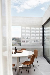 Thanks to the shutters that form private screens when viewed from the street, the residents can enjoy easy-breezy outdoor dining without having to worry about privacy.