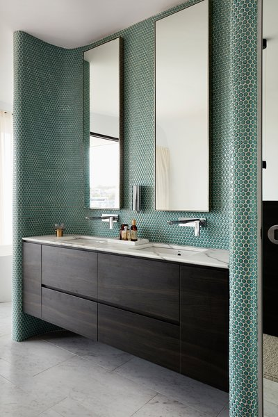 Emerald-green penny tiles line the walls in one of the sleek baths.