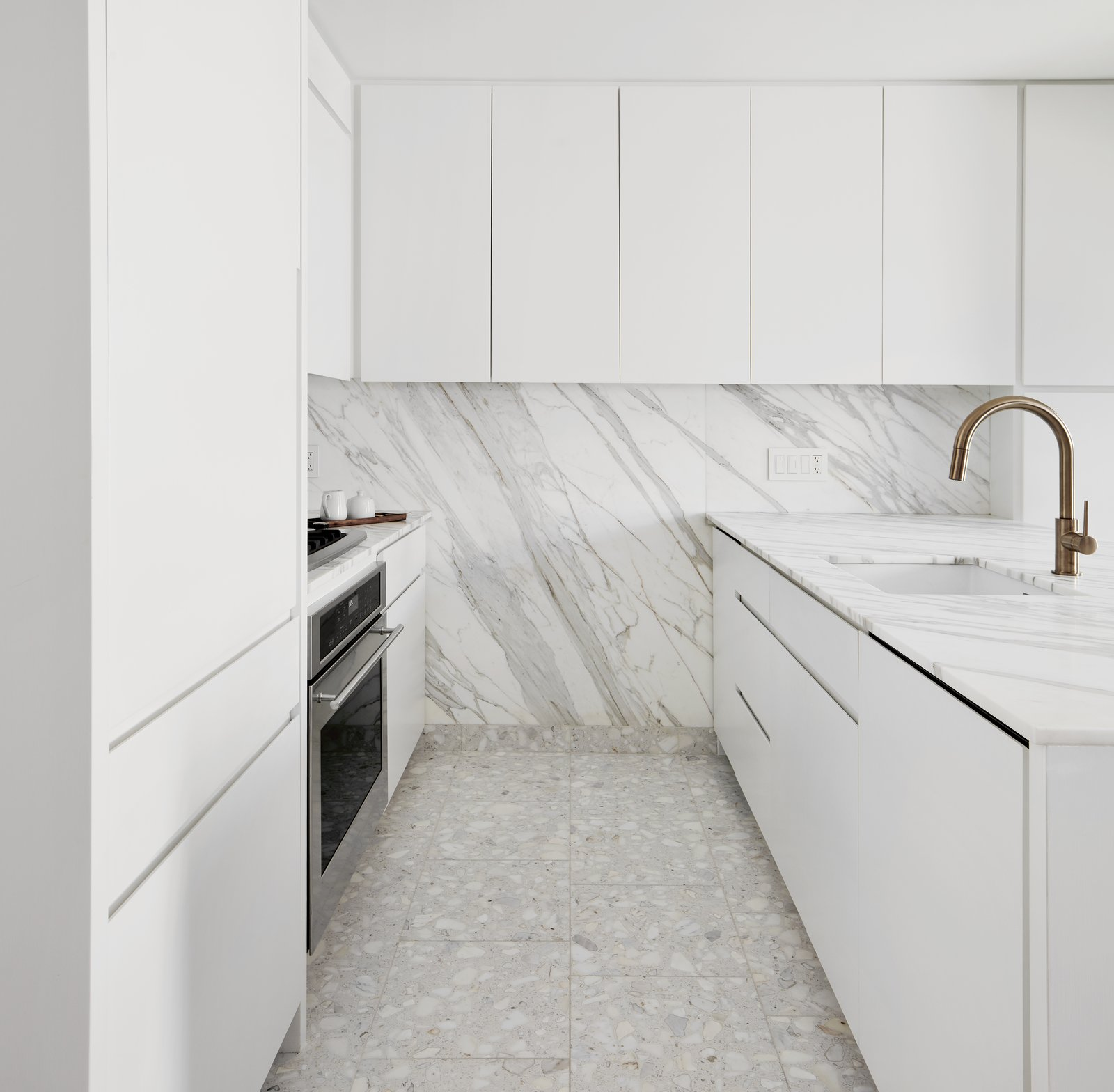 Kitchen, Cooktops, Terrazzo, White, Ceiling, Marble, Wall Oven, Marble, Undermount, and Refrigerator Terrazzo Floor / Marble Backsplash Kitchen  Kitchen Cooktops Undermount Wall Oven Marble White Photos from Chelsea Pied-à-Terre