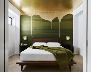 "Chelsea Pied-à-Terre's homeowners wanted STADT Architecture to incorporate a landscape feature to help mitigate downtown Manhattan's concrete landscape. Says the architects, ""our custom wall covering is analogous to the canopy bed's use of upholstery as a space defining ceiling canopy and headboard wall. For our design, collaborated with Calico Wallpaper, the gold-leafed ceiling creates a luminous sky above the bed while the green field anchors the headboard wall. When privacy is not a concern, this room-sized architectural canopy bed becomes a visual focal point from the open living room."""