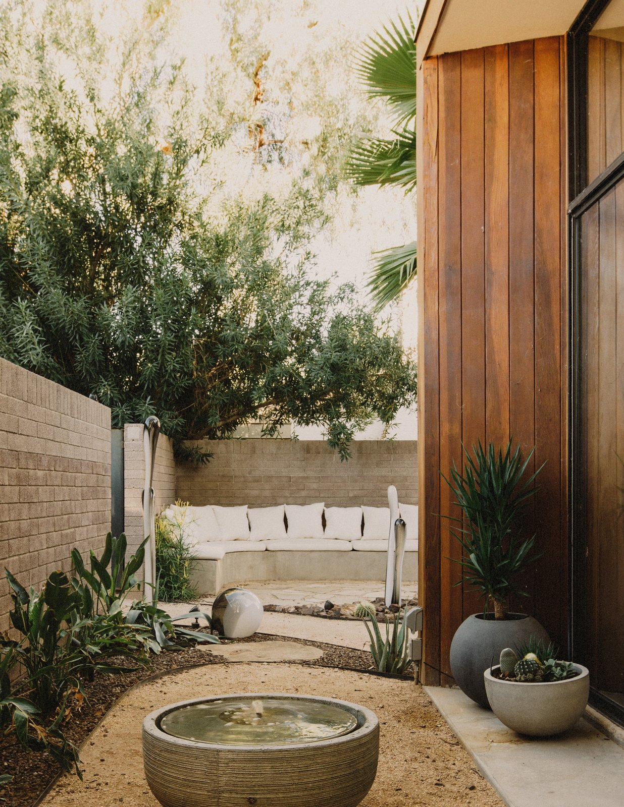 Outdoor, Front Yard, Desert, Raised Planters, Stone Patio, Porch, Deck, Decomposed Granite Patio, Porch, Deck, and Shrubs View from the office courtyard to the entry courtyard that features a custom concrete bench  Curves House by The Ranch Mine