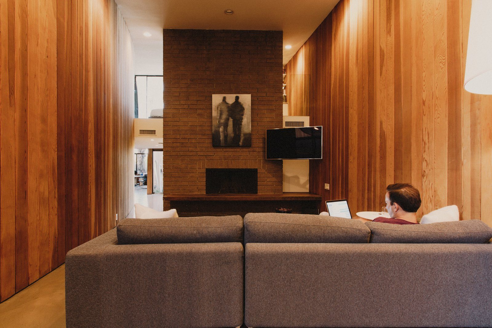 Living room clad with redwood on both sides with a concrete block fireplace in the center of the double height space Tagged: Living Room, Sofa, Ceiling Lighting, Concrete Floor, Standard Layout Fireplace, and Wood Burning Fireplace.  Curves House by The Ranch Mine