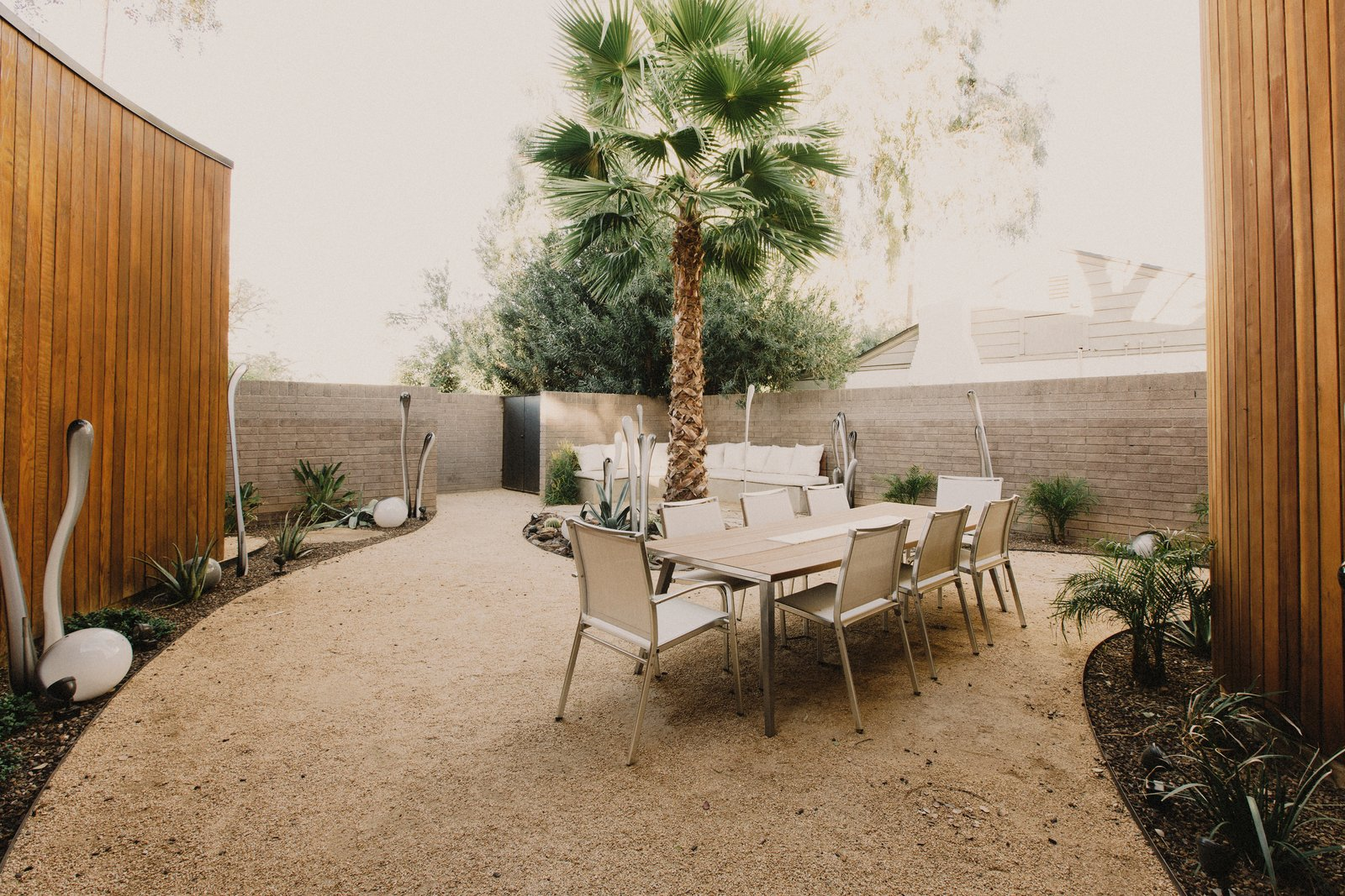 Outdoor, Desert, Shrubs, Trees, Decomposed Granite Patio, Porch, Deck, and Stone Patio, Porch, Deck Front courtyard extends living functions outside of the house, allowing the house to live much larger than its footprint  Curves House by The Ranch Mine