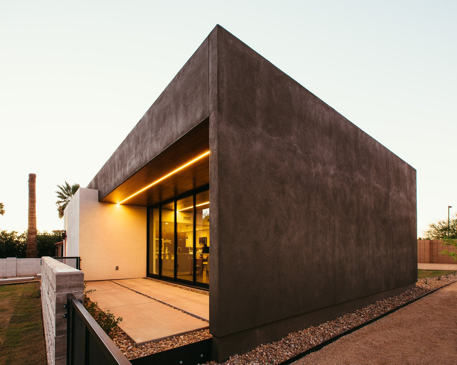 Concrete Patio, Porch, Deck, Ceiling Lighting, Trees, Concrete Floor, Grass, Front Yard, and Outdoor #modern #minimal #exterior #lighting #phoenix #arizona  Link House by The Ranch Mine