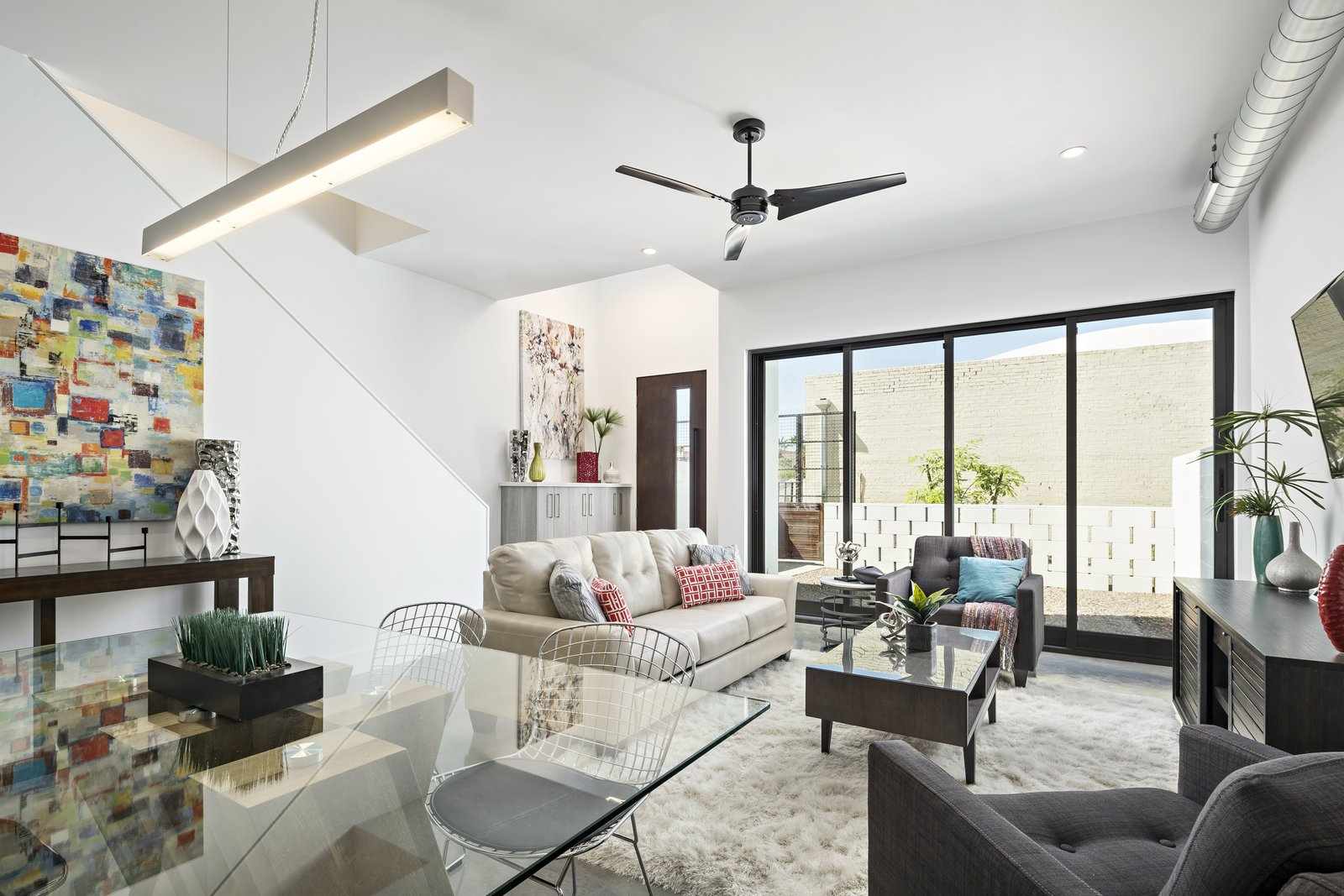 Living Room, Sofa, Chair, Concrete Floor, and Ceiling Lighting Sliding glass doors open up this living area to a private courtyard off of the pedestrian walkway  Uptown Row