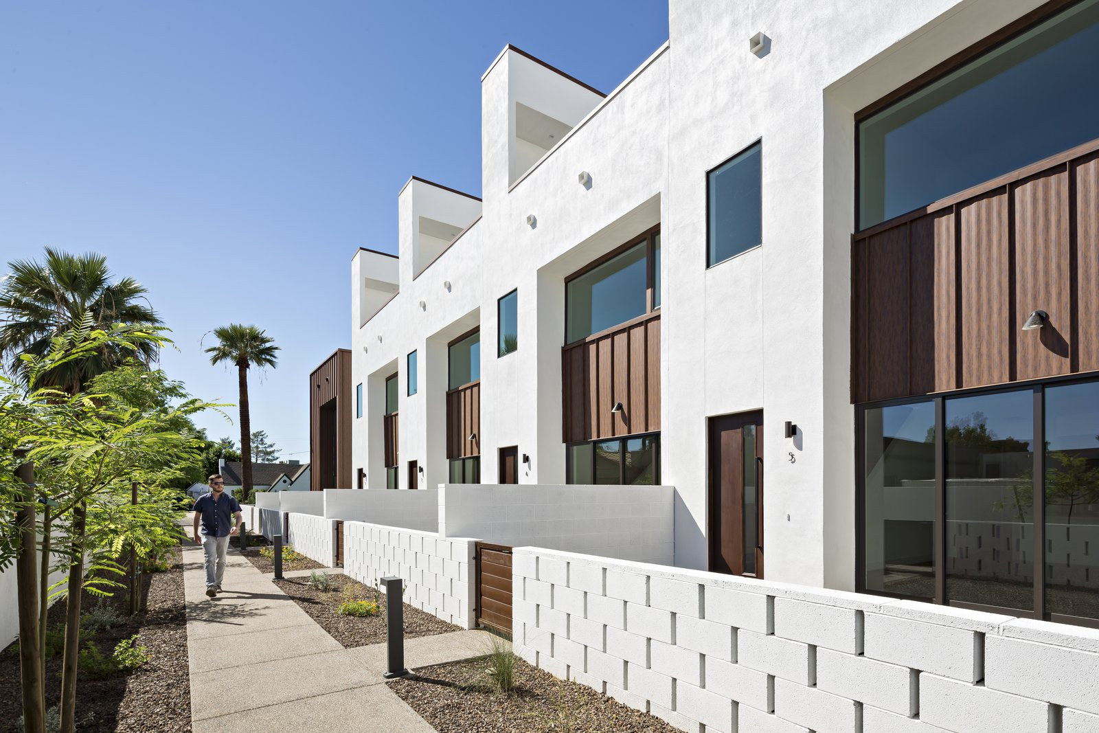 Outdoor, Front Yard, Trees, Desert, Shrubs, Flowers, Hardscapes, Horizontal Fences, Wall, Concrete Patio, Porch, Deck, and Decomposed Granite Patio, Porch, Deck Each unit in this development is accessed by a pedestrian walkway through a private courtyard. The low, spaced concrete block wall provides a social component to the development  Uptown Row