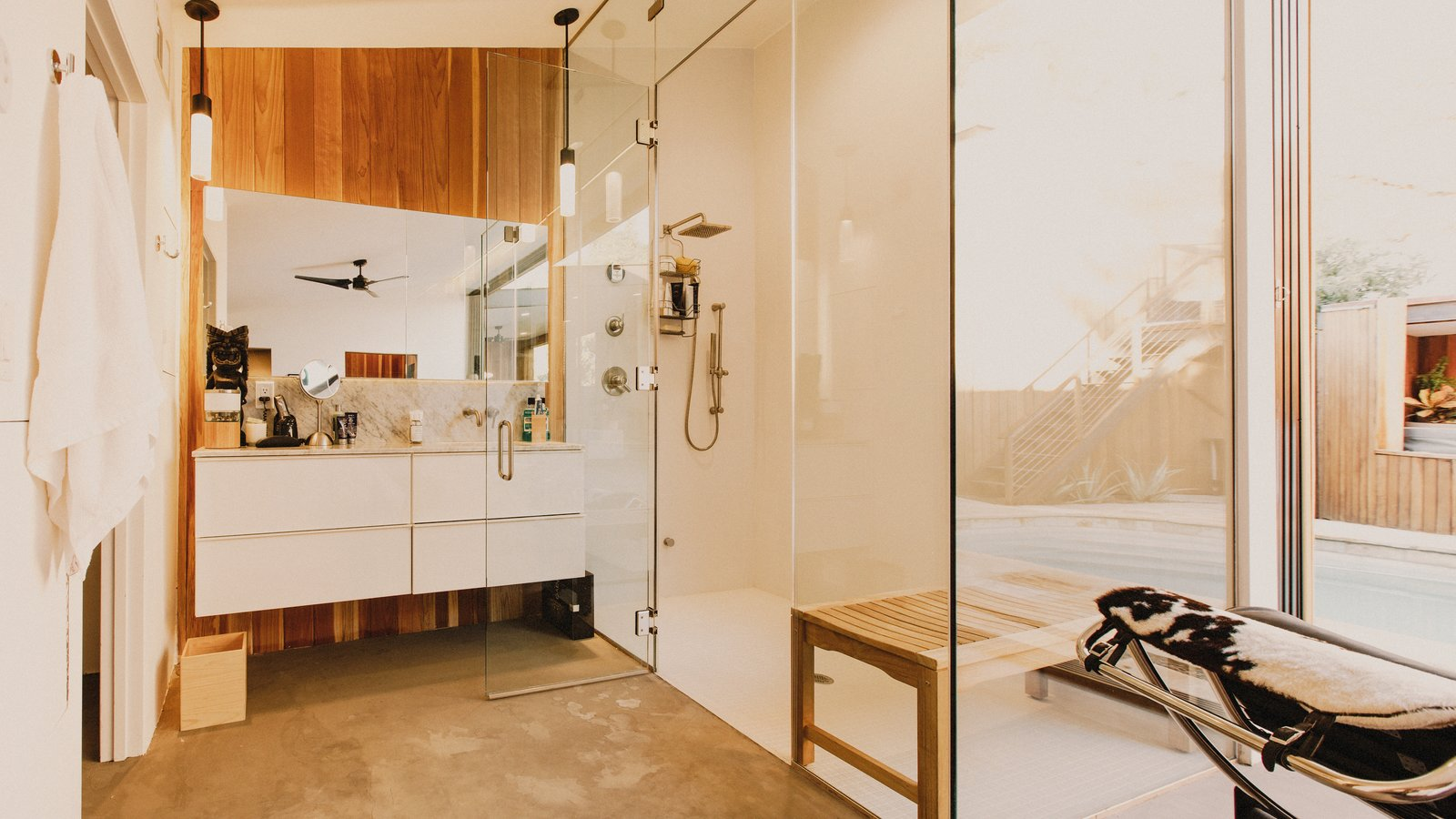 Bath Room, Concrete Floor, Undermount Sink, Pendant Lighting, Porcelain Tile Wall, Enclosed Shower, Marble Counter, Ceiling Lighting, and Two Piece Toilet Master bathroom featuring a steam shower  Curves House by The Ranch Mine