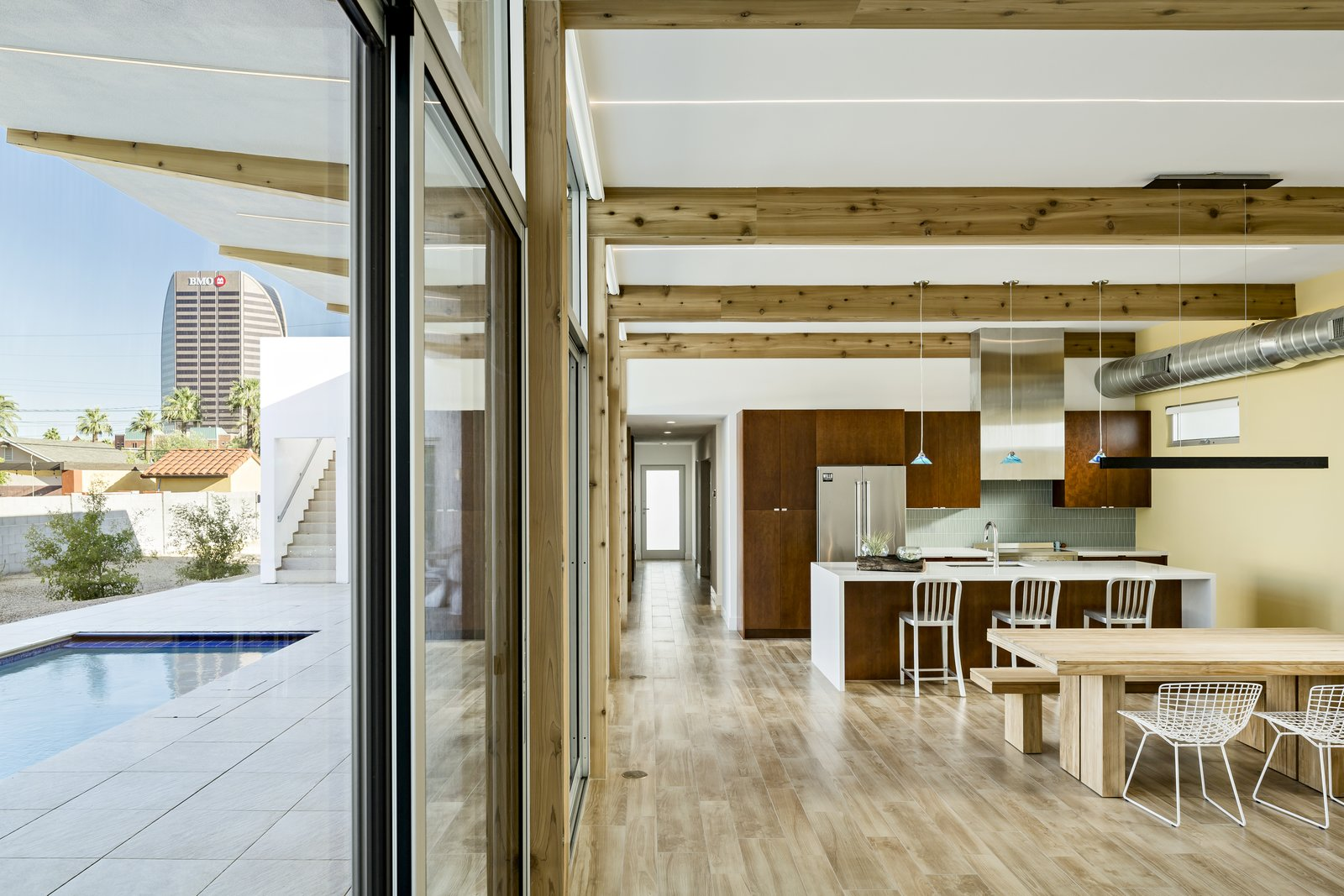 Dining Room, Ceiling Lighting, Table, Bench, Pendant Lighting, and Porcelain Tile Floor The wood beams flow from inside to outside and angle up to capture a view of the tallest tower in the area.  Sol House by The Ranch Mine
