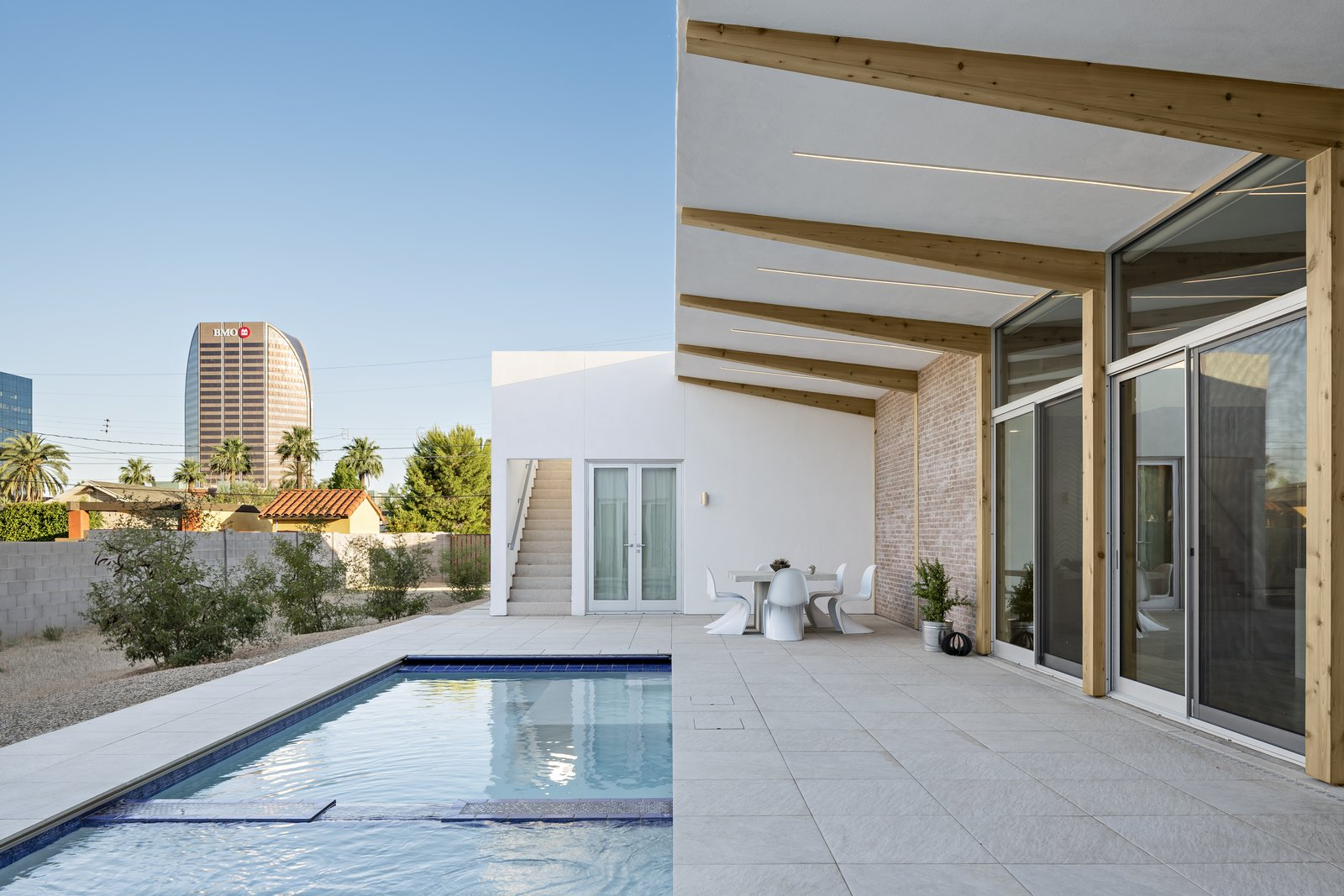 Outdoor, Side Yard, Desert, Trees, Small Pools, Tubs, Shower, Hardscapes, Decomposed Granite Patio, Porch, Deck, and Pavers Patio, Porch, Deck Cantilevered wood beams angle up towards the growing city skyline. On the left, a sloped area captures the monsoon rainfall and the Mulga Acacia trees will grow to the height of the home over time to provide more shade and privacy.  Sol House by The Ranch Mine