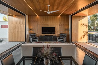 Walnut plywood with integrated LED lighting clad the open living space area, extending beyond the pocketing glass walls to the exterior