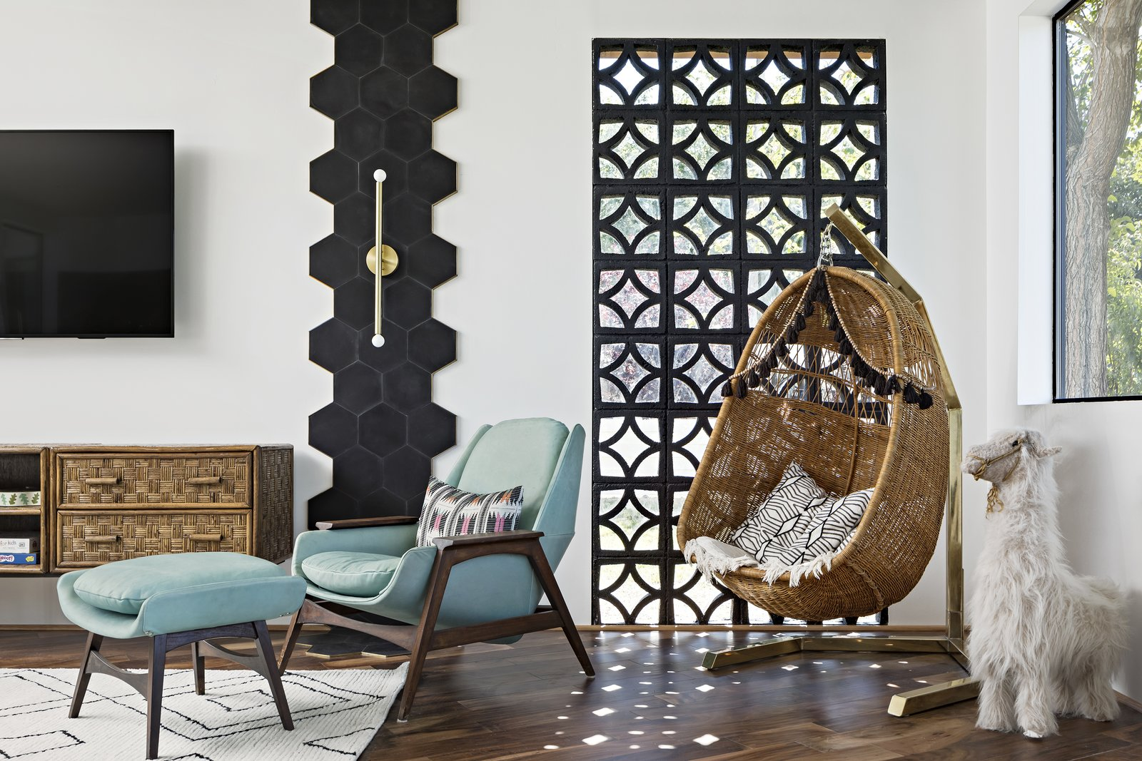 Living Room, Medium Hardwood Floor, Console Tables, Recliner, and Chair Reclaimed breeze block filters the morning light  Photo 3 of 11 in 5 Striking Designs That Use Perforated Cement Breeze-Blocks in Interesting Ways from Modern Manor