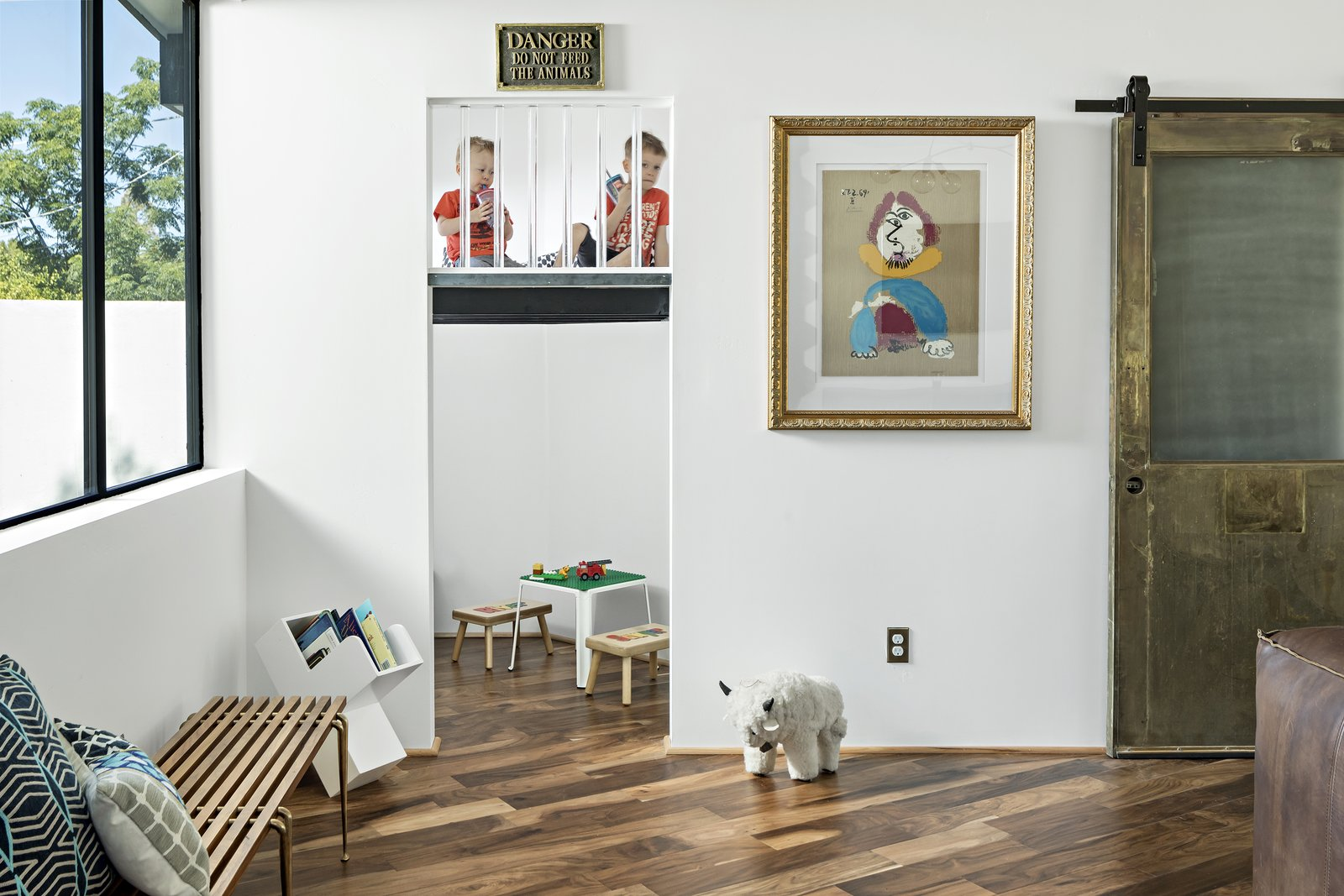 Kids Room, Playroom Room Type, Bench, Medium Hardwood Floor, Toddler Age, Pre-Teen Age, and Neutral Gender Kid's nook features a hidden brass ladder up to a lucite enclosed play space. Reclaimed brass door hides toy storage  Modern Manor by The Ranch Mine