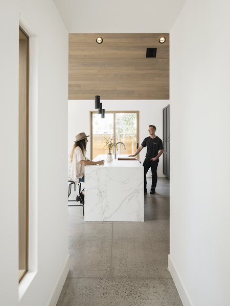 Waterfall edge on the Dekton counter. The floors are exposed aggregate concrete