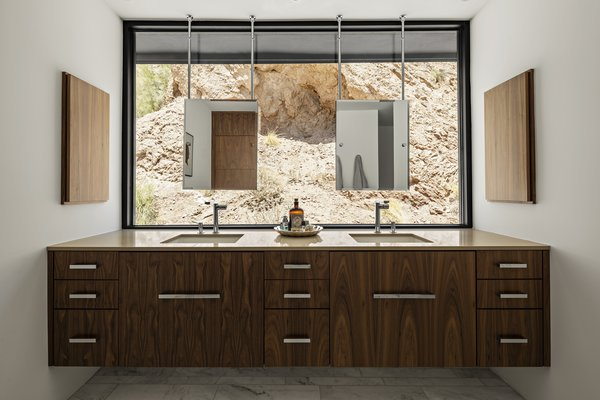 Mirrors hung in front of the new window in the master bathroom provide a view of the raw mountain face