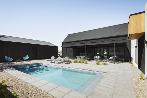 The L-shaped house plan with a detached garage create a 3 sided courtyard, providing privacy and shade in the urban, desert lot.  A small  pool is the focus of the backyard living