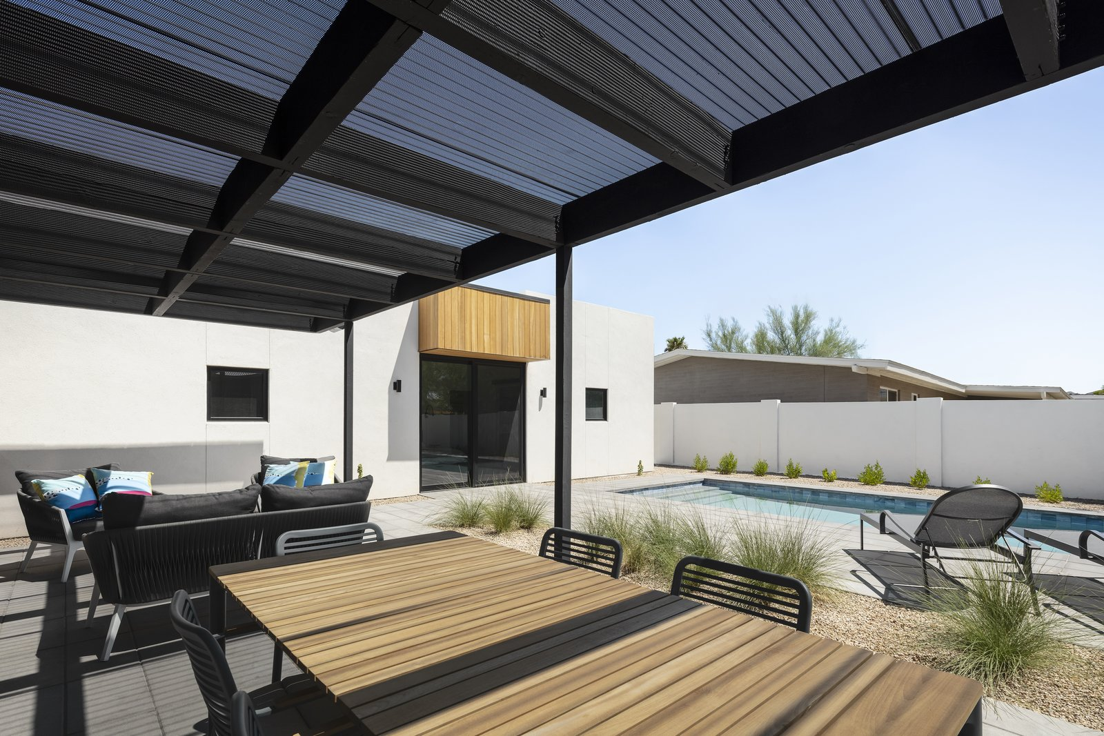 Outdoor, Hardscapes, Small Patio, Porch, Deck, Desert, Small Pools, Tubs, Shower, Pavers Patio, Porch, Deck, and Back Yard A perforated, corrugated metal patio cover provides a transition between the bright desert sun, and the shaded interior of the house  Photos from Pleats