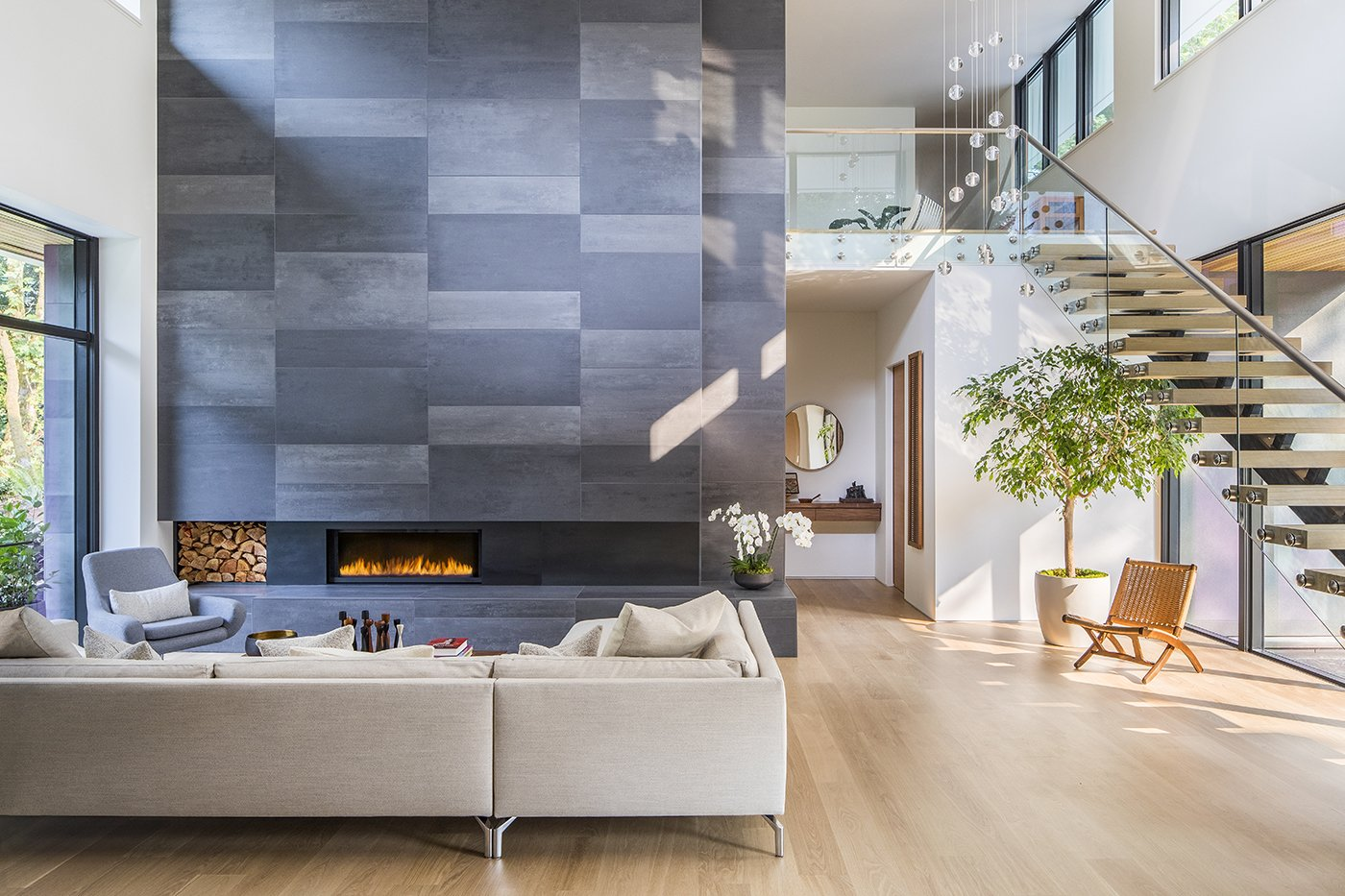 Living Room, Pendant Lighting, Light Hardwood Floor, Sectional, Gas Burning Fireplace, and Standard Layout Fireplace The double height hearth divides the main living spaces from the private bedrooms.   Wildwood by Giulietti / Schouten AIA Architects