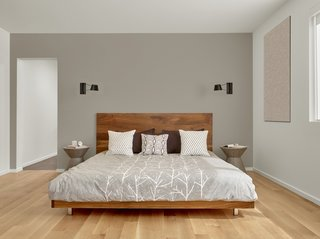 The walnut master bed frame is custom by Matt Eastvold. The sconces are by Brendan Ravenhill.