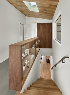 The sliding door and open shelves are by Matt Eastvold and are made of solid walnut. The ceiling features prefinished white oak and the floor is a thin cementitous product Ardex. this space serves as the main core of the home and connection between the living areas, entry, and bedroom areas.