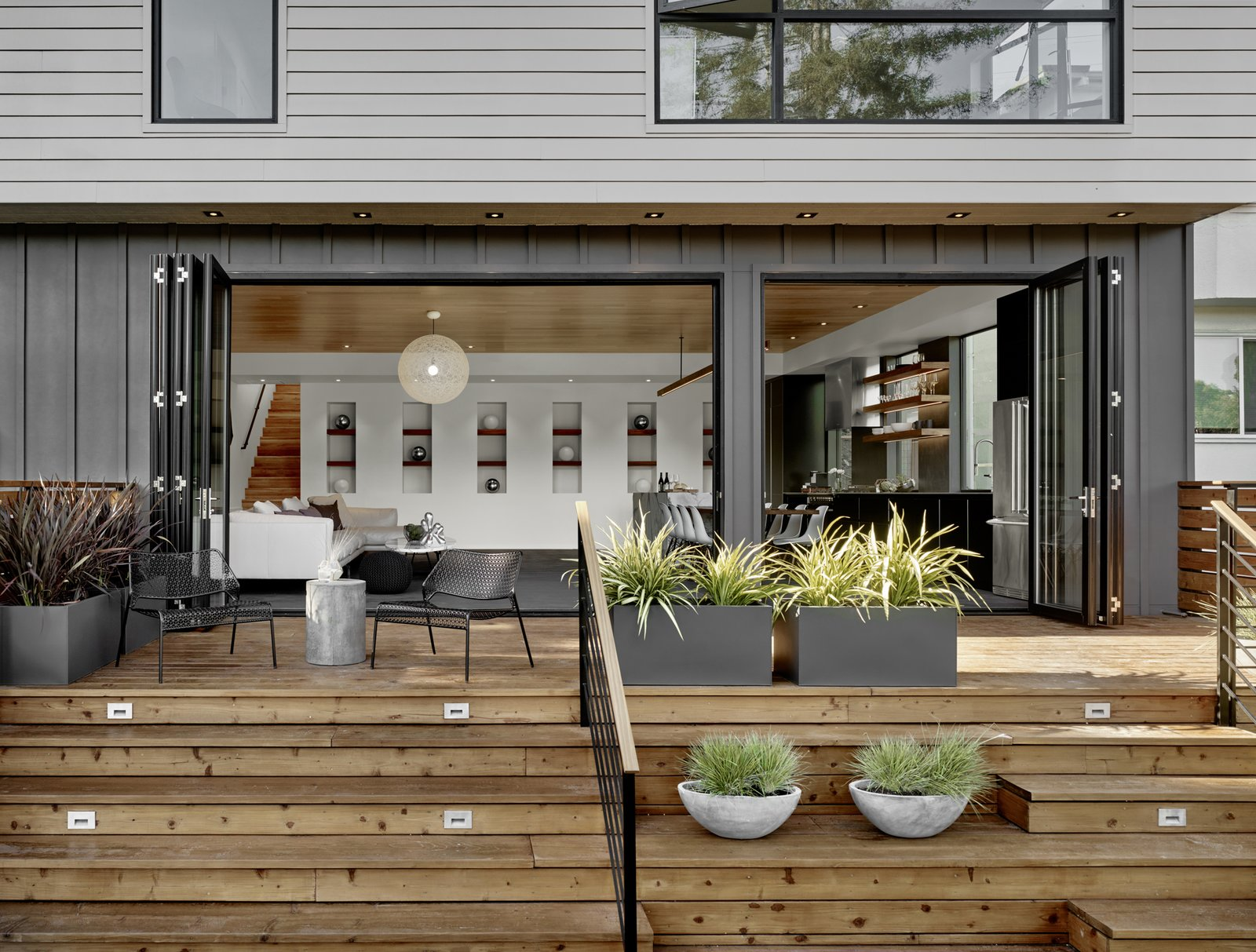 Outdoor The back of the house features a combination of Hardi-Panel lap siding and board and batten, which are in a series of greys softened by the redwood deck and plantings.  Trestle Glen Modern by Knock Architecture + Design