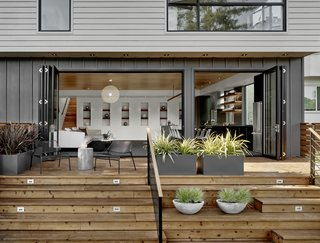 The back of the house features a combination of Hardi-Panel lap siding and board and batten, which are in a series of greys softened by the redwood deck and plantings.
