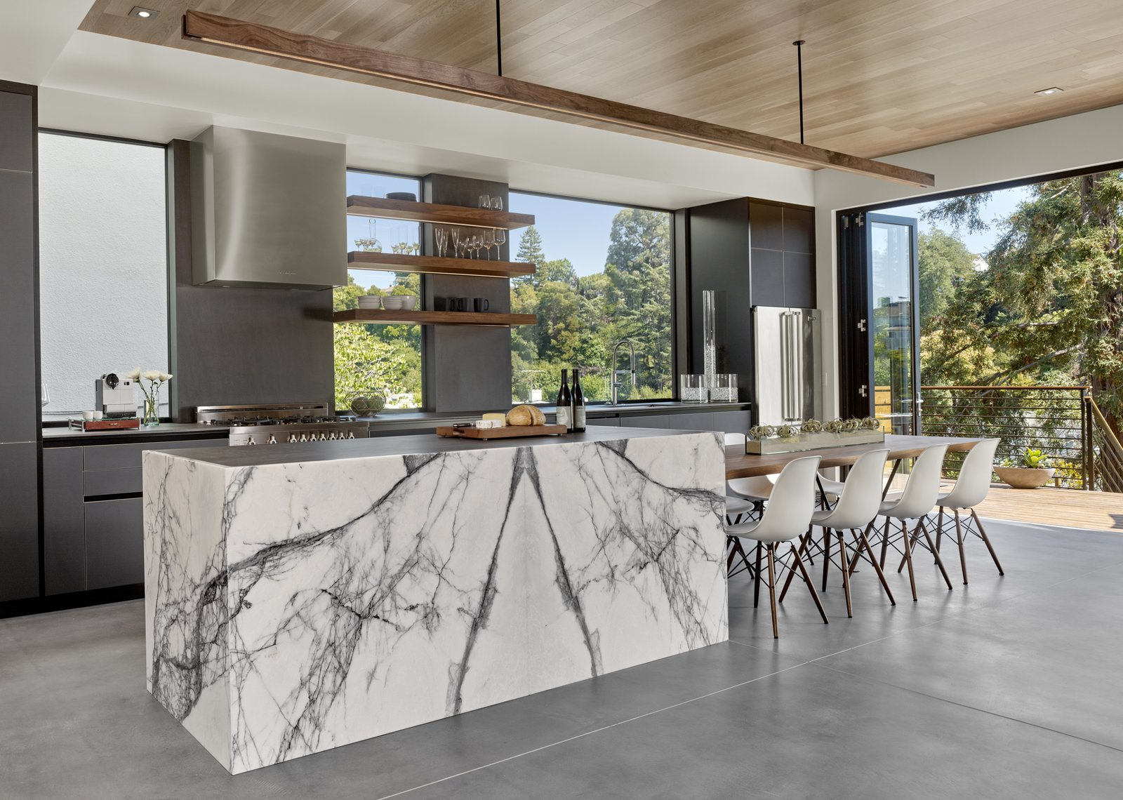 Kitchen, Range Hood, Refrigerator, and Marble Counter The cabinets are black matte glass by Leicht. The floating walnut table, shelves and light are by Matt Eastvold.  Trestle Glen Modern by Knock Architecture + Design